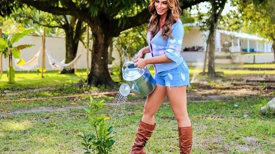 Modelo Nicole Bahls rega planta de plástico e ri de si mesma
