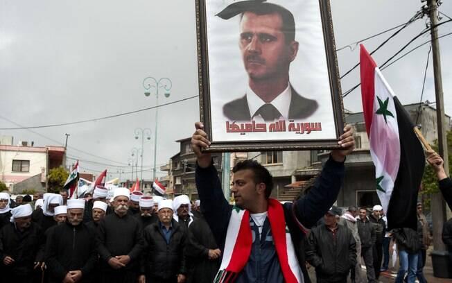 Druso carrega retrato do presidente sírio em que se lê 'Síria, Deus protege você', nas, Colinas do Golan (17/04)