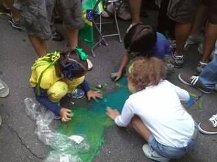 Crianças pintam cartaz em manifestação em São Paulo, no domingo (15)
