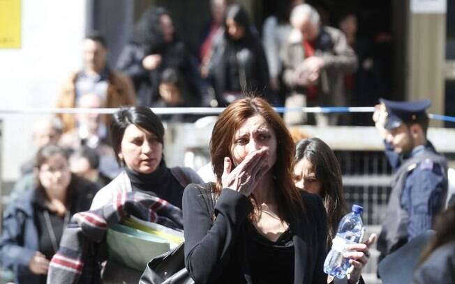 Mulher chora ao sair do edifício de um tribunal em Milão, Itália, depois de um homem abrir fogo no local