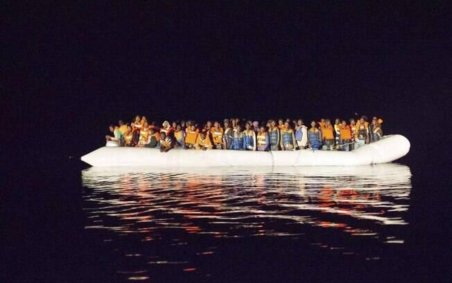 Barco com refugiados cruzando o Mediterrâneo na costa da Itália