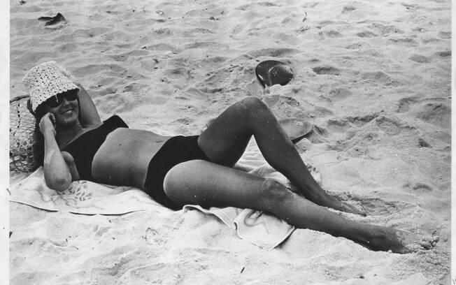 Helô Pinheiro, aos 17 anos, na praia de Ipanema: biquini, toalha e chapéu de palha