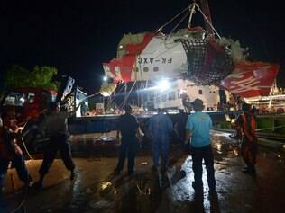 The tail section of the Air Asia Airbus A320 flight QZ8501 is prepared to be loaded onto a truck at port in Kumai on January 11, 2015. Indonesian divers on January 11 found the crucial black box flight recorders of the AirAsia plane that crashed in the Java Sea a fortnight ago with 162 people aboard, the transport ministry said. AFP PHOTO / ADEK BERRY