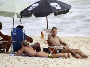 Felipe Titto toma sol na praia da Barra da Tijuca com a mulher