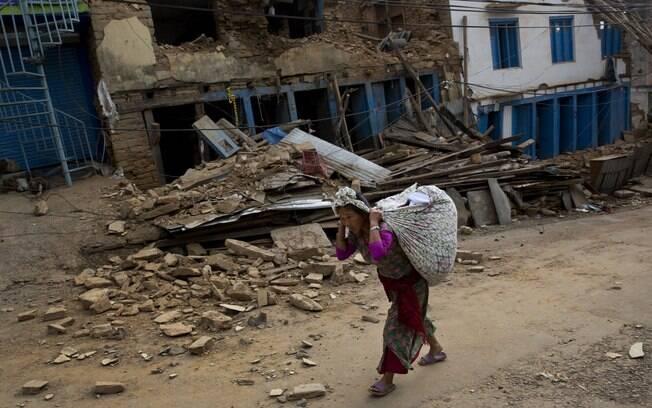 Mulher carrega pertences em cidade do Nepal destruída por dois terremotos em menos de um mês (13.5.2015)