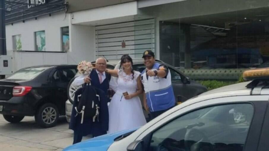Casal posando com agente de segurança