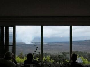 Com conforto. Hóspedes do hotel Volcano House admiram a cratera Halemaumau de uma sacada dentro do próprio estabelecimento