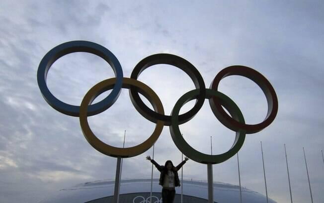 Mulher posa ao lado dos anéis olímpicos em Sochi, na Rússia