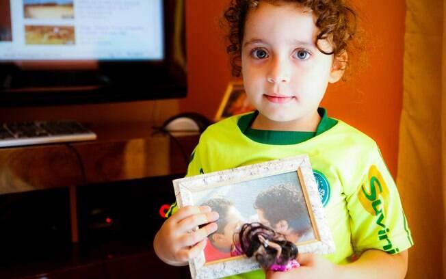Kaylla mostra a foto das mães. Na outra mão, uma boneca