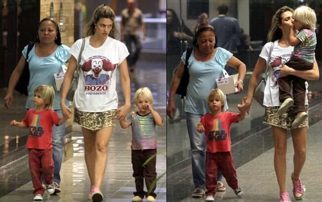 Fernanda Lima circula com os gêmeos e a babá pelo shopping