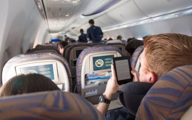 Pessoas sentadas nas suas poltronas do avião.