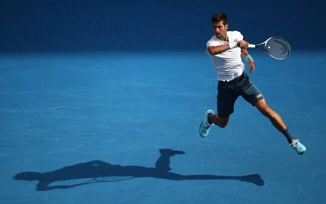 Novak Djokovic salta para devolver bola durante partida do Aberto da Austrália