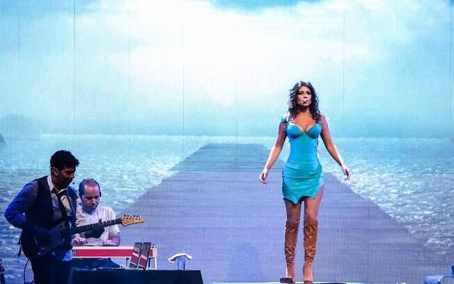 Ao tirar o casaco, a cantora revelou um vestido justo e de estilo ousado