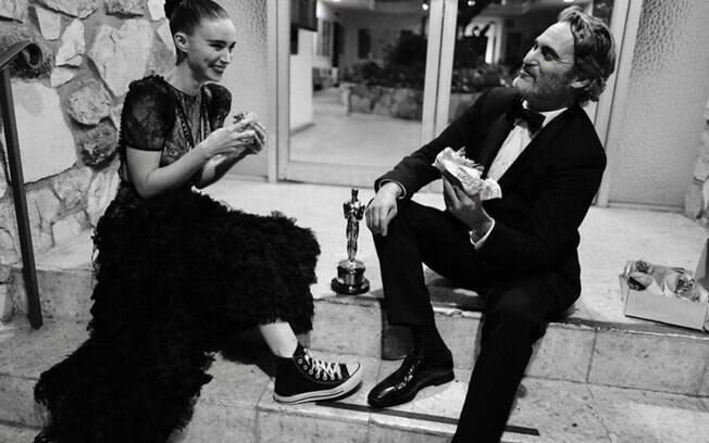 Joaquin Phoenix junto com a noiva comendo um hambúrguer vegano