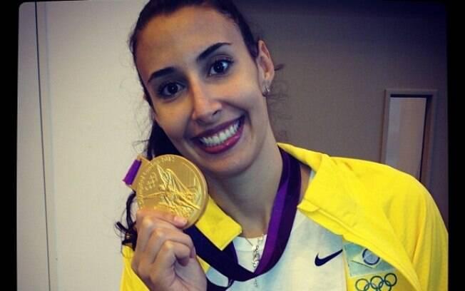 Jogadora exibe foto da medalha de ouro  conquistada nas Olimpíadas de Londres