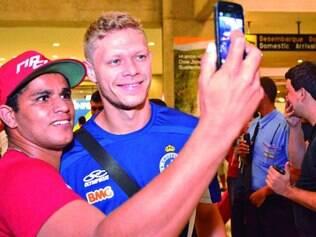 Começo promissor. Feliz com a estreia celeste no Brasileirão, torcedor faz foto com Marlone no desembarque do time em Confins