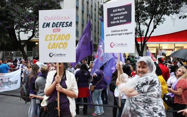 mulher segurando cartaz em manifestação