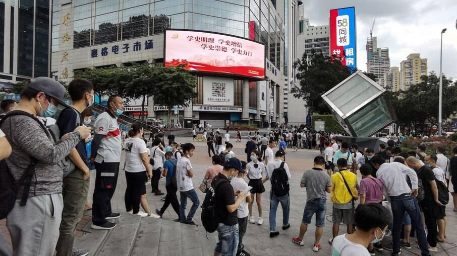 Pessoas do lado de fora do SEG Plaza de 300 metros de altura depois que ele começou a tremer, em Shenzhen