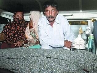 Marido de Farzana, Mohammad Iqbal, ao lado do corpo da mulher