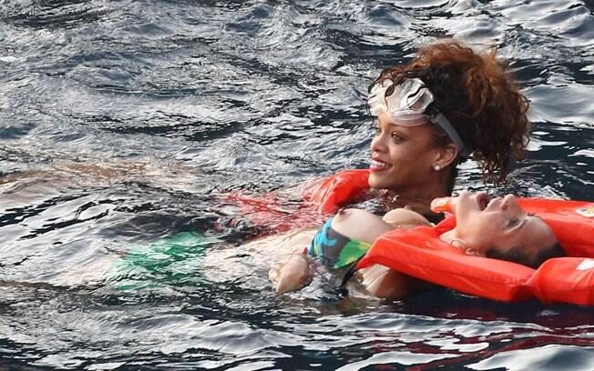 Rihanna nada, enquanto amiga não percebe que está mostrando um pouco demais