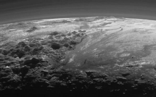 Luz solar do fundo destaca camadas da atmosfera de Plutão e terreno diverso