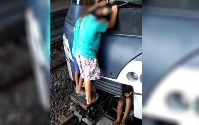 Meninos ficaram pendurados em trem, que sai da estação em velocidade