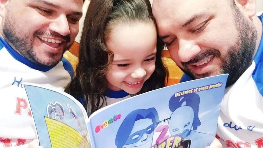 O autor, Alexandre, sua filha, Sara, e o marido, Renato, lendo o livro