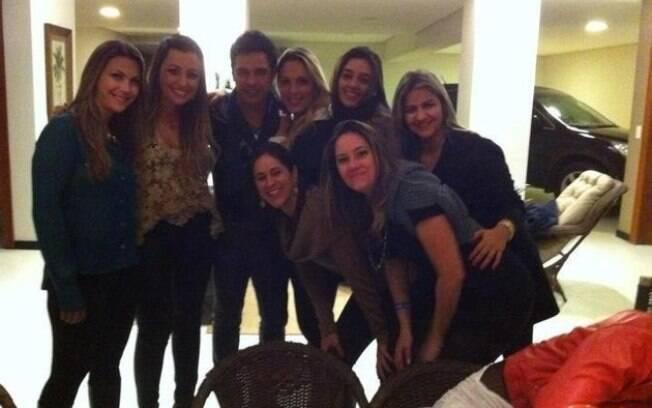 Zezé di Camargo tira foto com algumas mulheres. Gracielle (de jaqueta vermelha) se abaixa para não aparecer na imagem