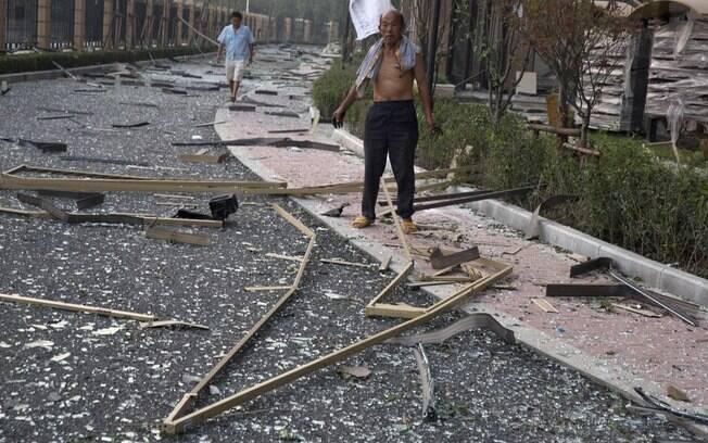 Homem vê vidros quebrados depois de uma explosão que quebrou janelas em um complexo residencial de Tianjin, China (13/08). Foto: AP
