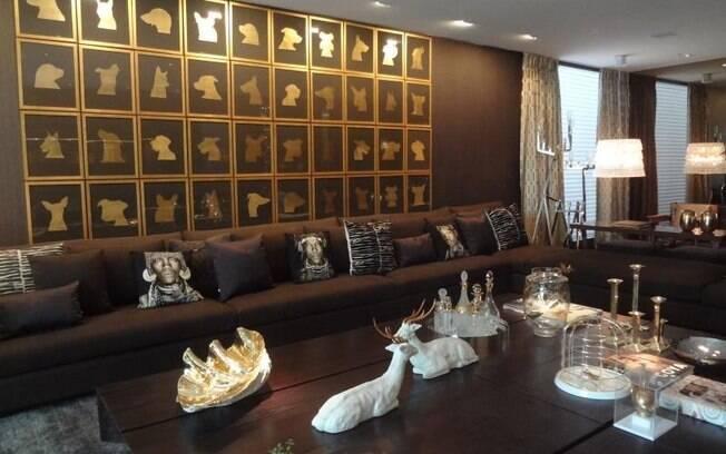 Para compor com os móveis de madeira e os revestimentos marrom, a arquiteta Brunete Fraccaroli usou diversas peças em dourado