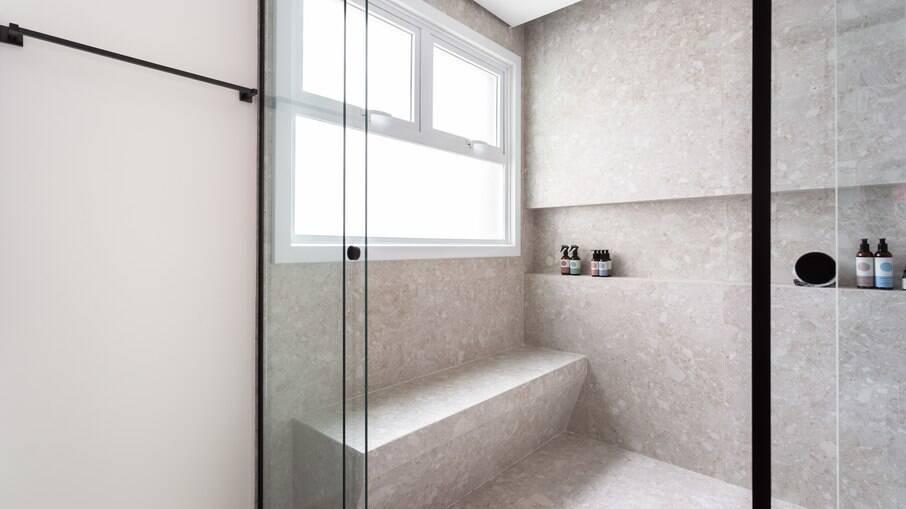 Com ampla janela, as arquitetas do Studio Tan-gram não hesitaram em escolher o box até o teto. O banheiro ainda recebeu a instalação de um banco dentro da área de banho. Mais conforto impossível