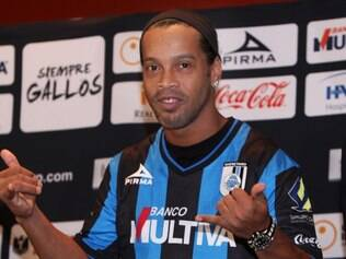 Brazil's Ronaldinho dons his new Queretaro soccer club jersey at a press conference in Mexico City, Friday, Sept. 12, 2014. Mexican first-division club Queretaro signed the former 34-year-old Brazil star, who had been without a club since leaving Brazil's Atletico Mineiro in July and had been negotiating with several clubs. The two-time FIFA world player of the year helped Atletico Mineiro win last year's Copa Libertadores for the first time. (AP Photo/Marco Ugarte)