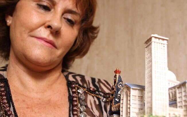 Márcia Fernandes observa uma réplica do Santuário de Nossa Senhora Aparecida e imagem da santa: amor e humildade
