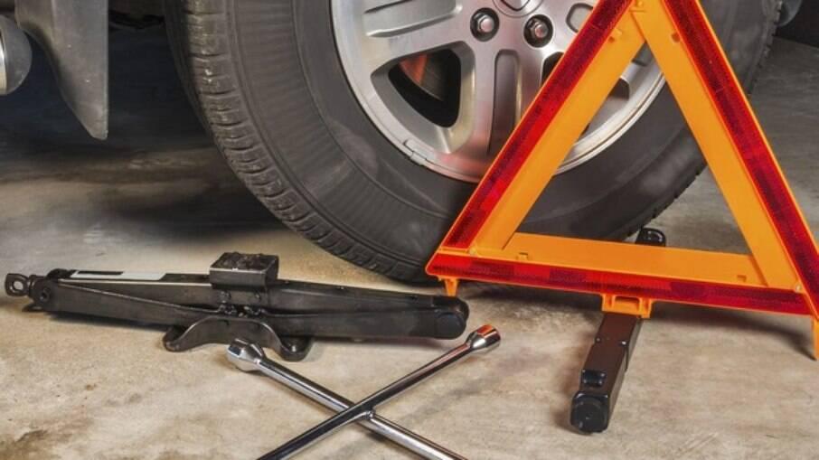 Kit completo para a troca do pneu, que inclui macaco, chave de roda e triângulo