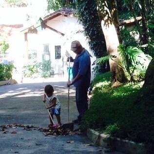 Com uma vassourinha, Dom ajuda a tirar a folhagem da rua