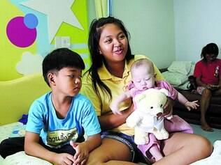 Família. A barriga de aluguel tailandesa Pattaramon Chanbua, 21, com seu filho mais velho, Game, 7, e o bebê Gammy, 7 meses