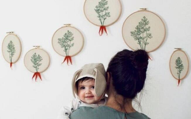 Veselka Bulkan e sua filha, já com seis meses, em frente a outros bordados feitos pela alemã