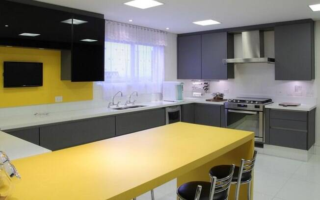Para mais ousadia na decoração de cozinha, mesa e parte da parede amarelas