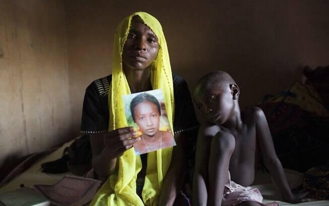 Rachel Daniel, 35, segura foto da filha, Rose Daniel, 17, com o filho ao seu lado, Bukar, 7, na casa da família em Maiduguri, Nigéria (maio/2014)