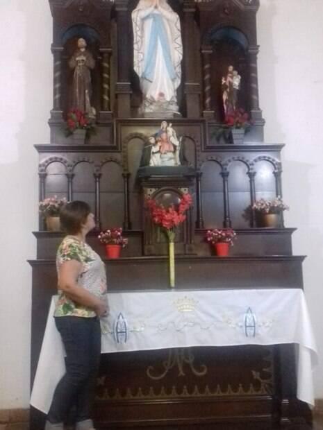 Mulher encara imagens de santos em igreja