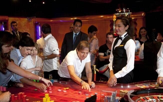 Roberto Carlos faz sua jogada no Cassino do navio; ao fundo, Tom Cavalcante e a mulher, Patrícia