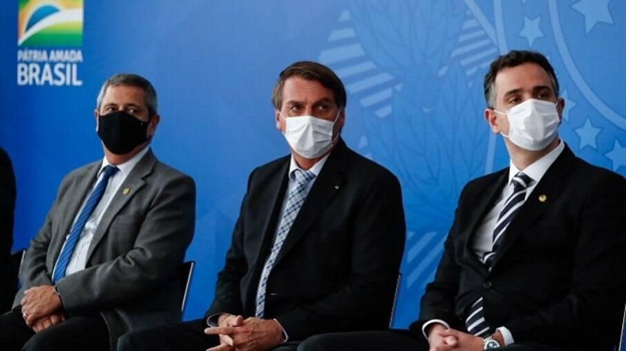 Bolsonaro de máscara sentado entre o ministro Braga Netto (Casa Civil) e o presidente do Senado Rodrigo Pacheco