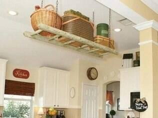 A escada de madeira foi pendurada em correntes e permitiu guardar mais objetos na cozinha
