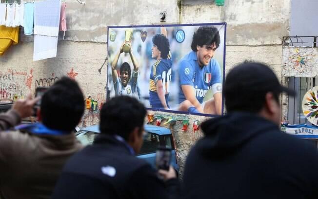 Torcedores do Napoli, clube onde o argentino fez história, tiram fotos de mural do jogador na cidade italiana