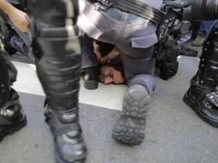 A protester is detained by police during a demonstration demanding better public services and protesting the money spent on the World Cup soccer tournament in Sao Paulo, Brazil, Thursday, June 12, 2014. Brazilian police clashed with anti-World Cup protesters trying to block part of the main highway leading to the stadium that hosts the opening match of the tournament. (AP Photo/Nelson Antoine)