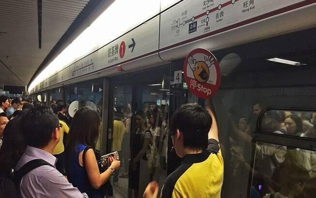 As portas da plataforma do metro com o guarda sinalizando com a placa