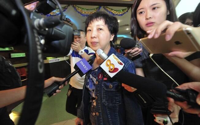 Jornalistas tentam entrevistar familiares dos passageiros do voo 8501 da AirAsia no aeroporto de Cingapura. Foto: AP Photo/Xinhua, Then Chih Wey