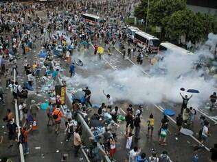 Image Description :	Riot police use tear gas against protesters after thousands of people block the main road at the financial Central district Hong Kong, Sunday, Sept. 28, 2014. Hong Kong activists kicked off a long-threatened mass civil disobedience protest Sunday to challenge Beijing over restrictions on voting reforms, escalating the battle for democracy in the former British colony after police arrested dozens of student demonstrators. (AP Photo/Vincent Yu)