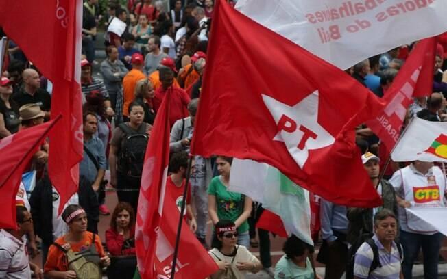 Manifestantes exibem bandeira do PT durante ato; integrantes do partido dividiram propina, diz Lava Jato