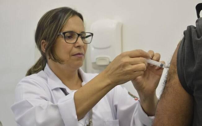 Profissional de saúde aplica vacina no braço de uma pessoa